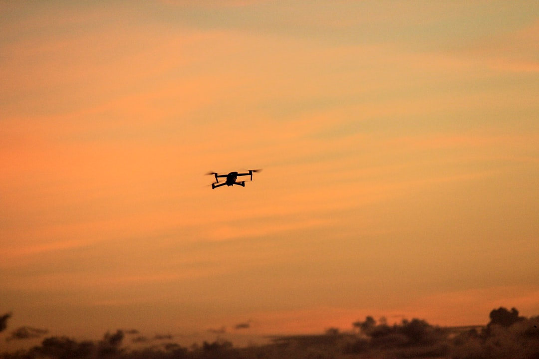 A plane flying in the air with a sunset in the background
